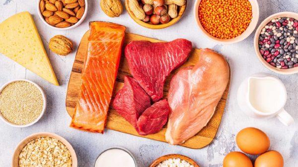 Alimentos ricos em vitamina D como salmão, carne vermelha, laticinios, ovos sobre uma mesa.
