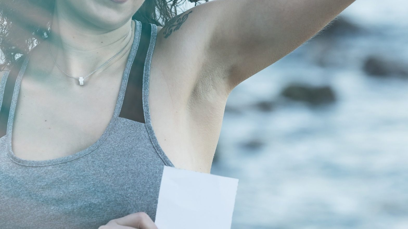 Mulher com o braço levantado para cima mostrando sua axila escura.