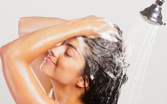 Mulher lavando o cabelo no chuveiro.