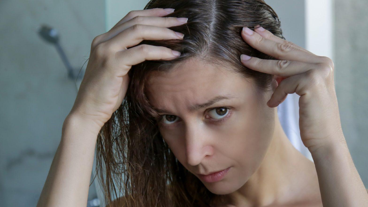 Mulher observando a raiz do seu cabelo oleoso.