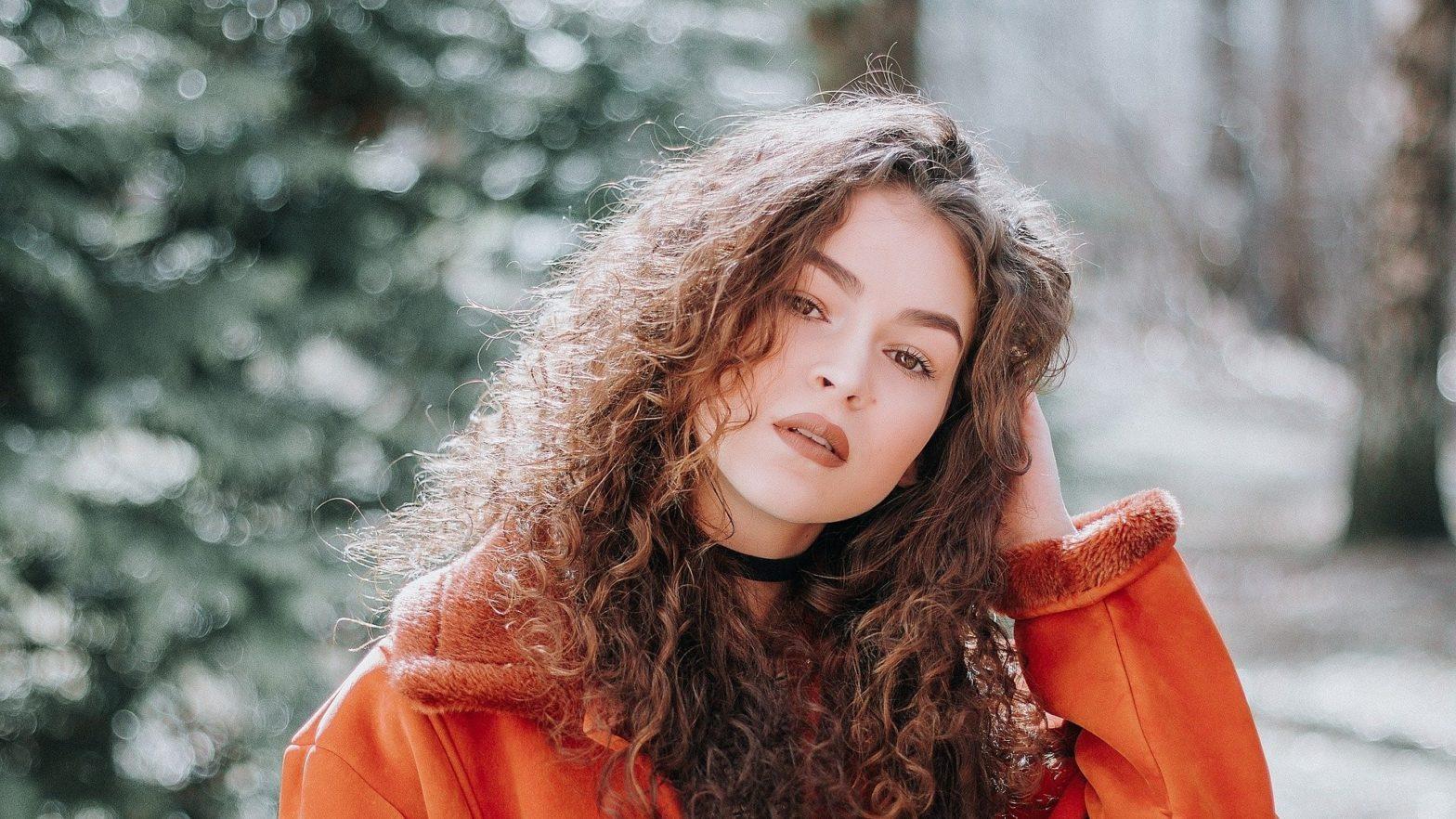 Menina de cabelos cacheados e jaqueta laranja.
