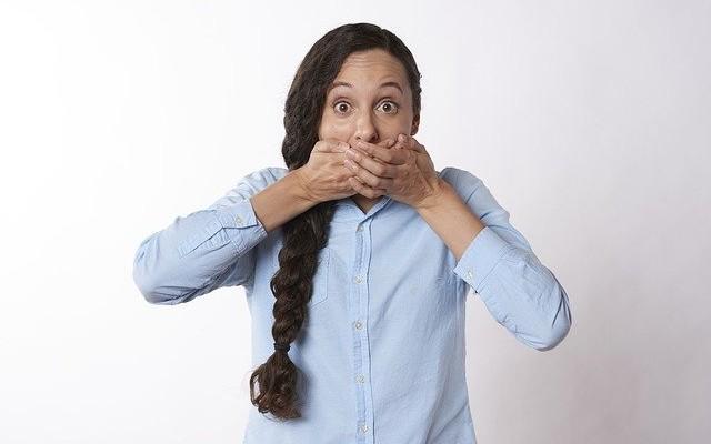 Mulher tampando a boca com as mãos.