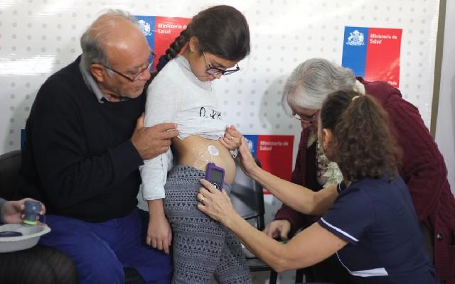 Enfermeira colocando a bomba de insulina em uma criança com diabetes.