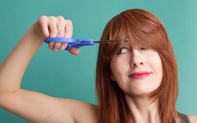 Mulher com tesoura para cortar a franja.