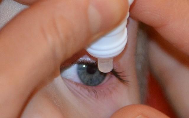 Aplicação de um colirio para glaucoma no olho de uma criança.