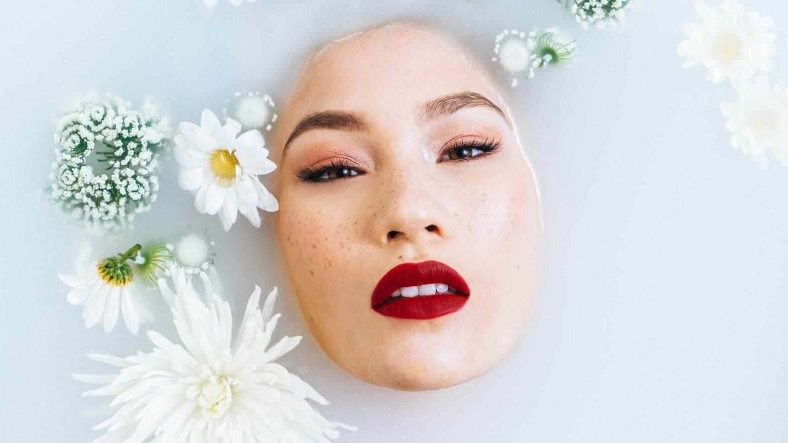 Mulher com maquiagem vegana dentro de uma banheira com água e flores.