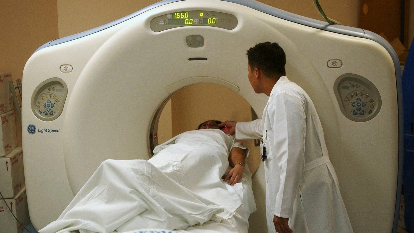 Paciente deitado na maca de tomografia. Radiologista ao lado.