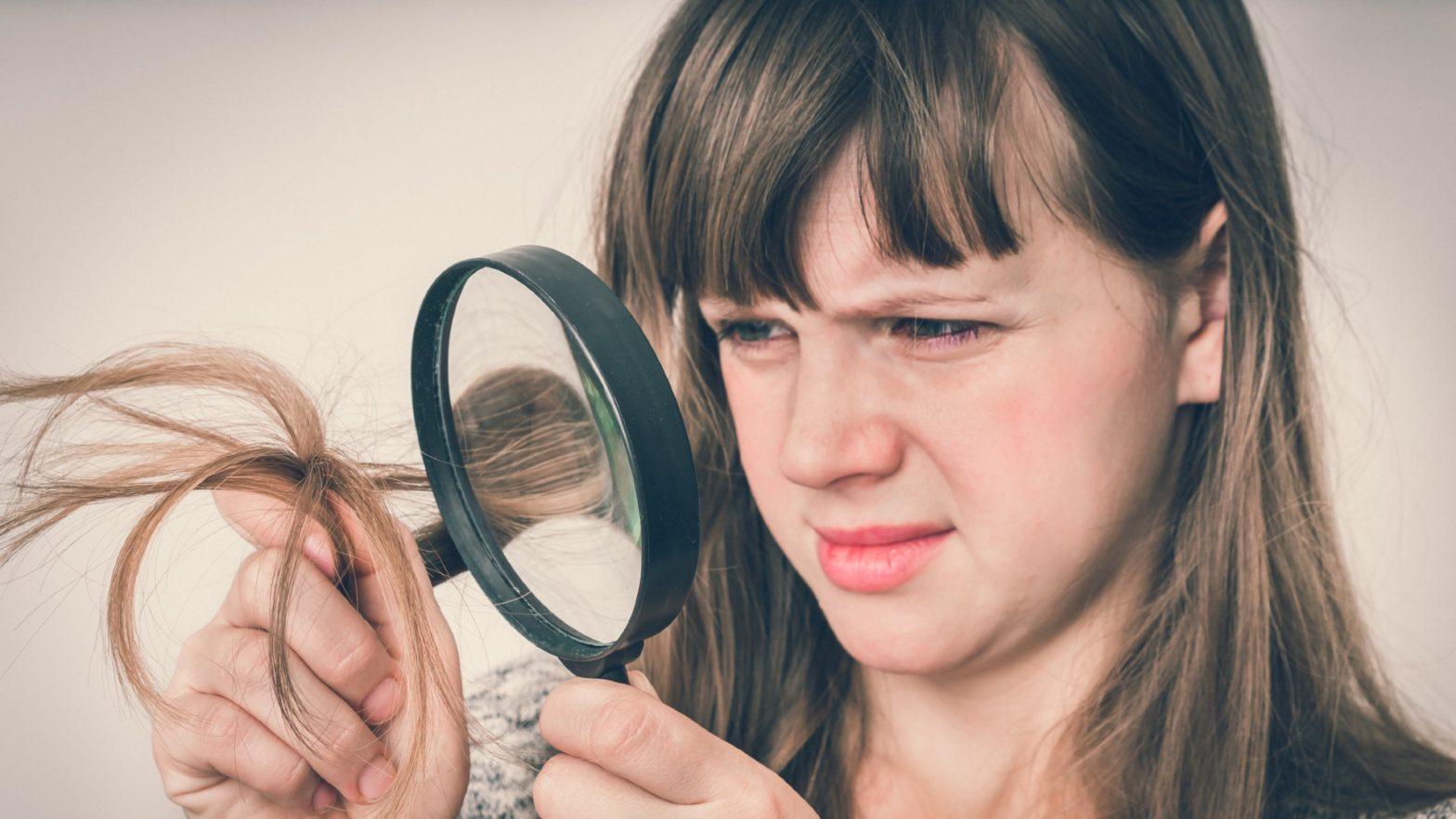 Mulher com uma lupa observando as pontas do seu cabelo.