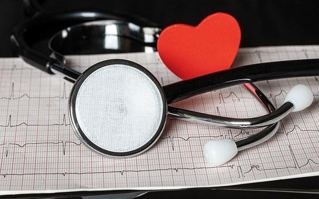 Estetoscópio e um objeto em forma de coração.