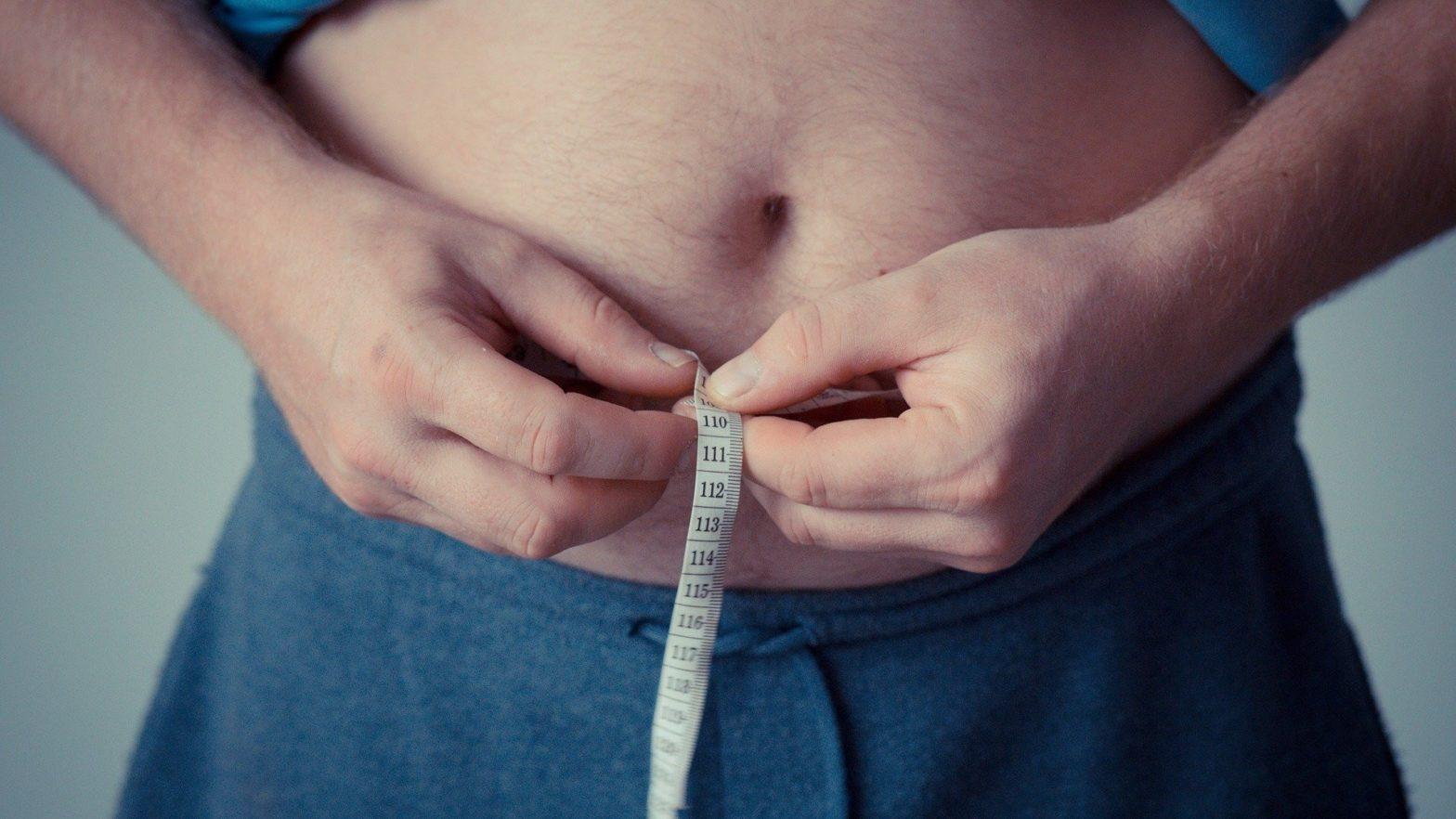 Homem medindo a circunferência abdominal
