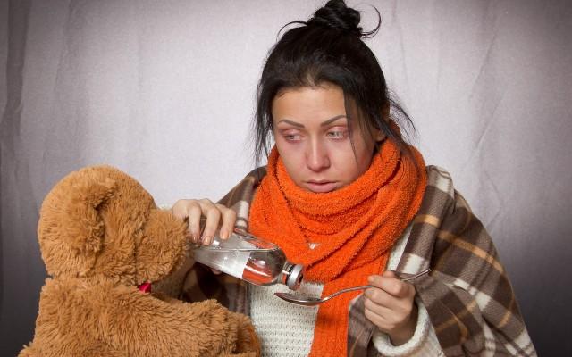 Mulher com mal-estar colocando soro em uma colher para aliviar os sintomas provocados pelo citomegalovírus.