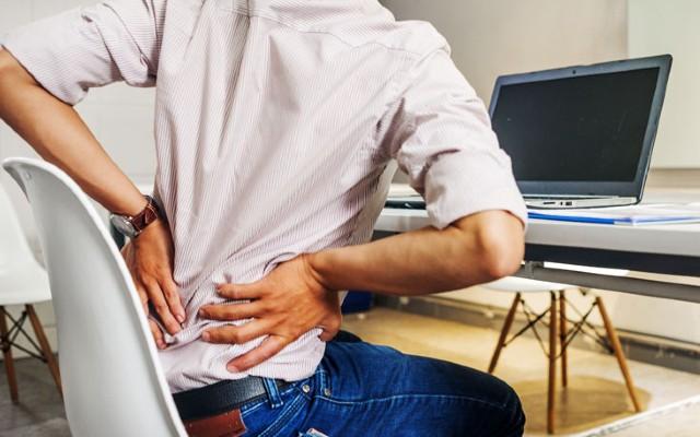 Homem sentado com as mãos na lombar sentindo dor.