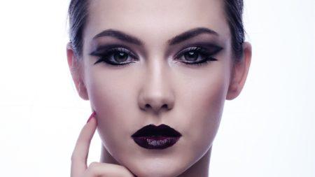 Rosto de mulher com maquiagem preta.