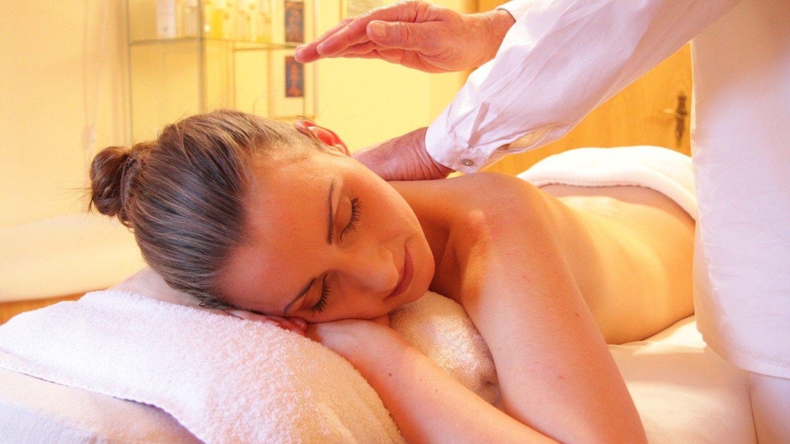 Mulher deitada recebendo massagem modeladora de uma profissional em uma clinica estética.