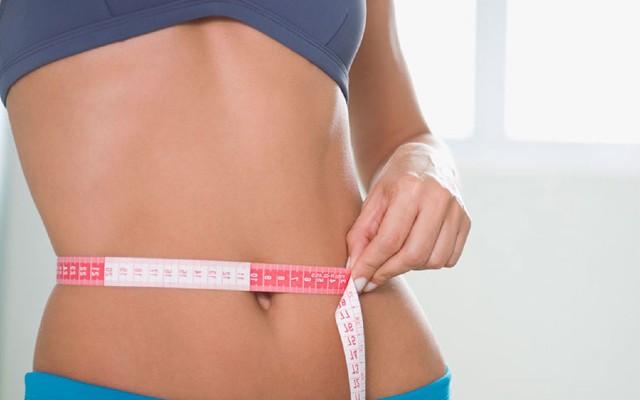 Mulher medindo a circunferência do abdômen.