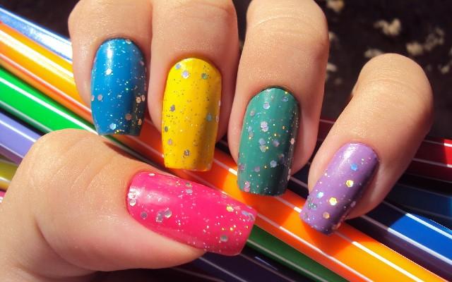 Unhas longas pintadas com esmaltes coloridas.