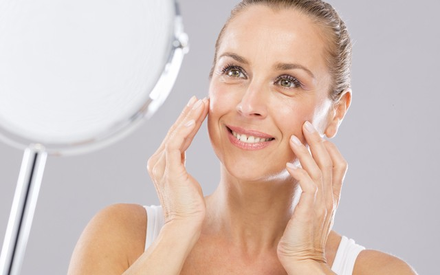 Mulher sorrindo em frente ao espelho praticando yoga facial.
