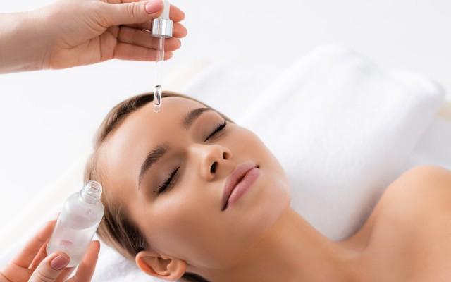 Profissional estética aplicando ácido glicólico no rosto da paciente.