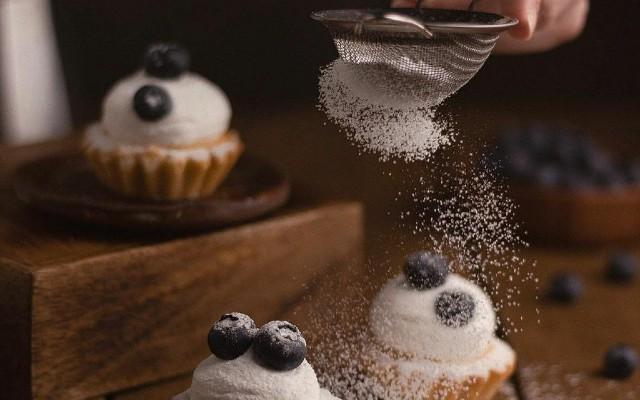 Confeiteira peneirando açúcar em cupcakes.