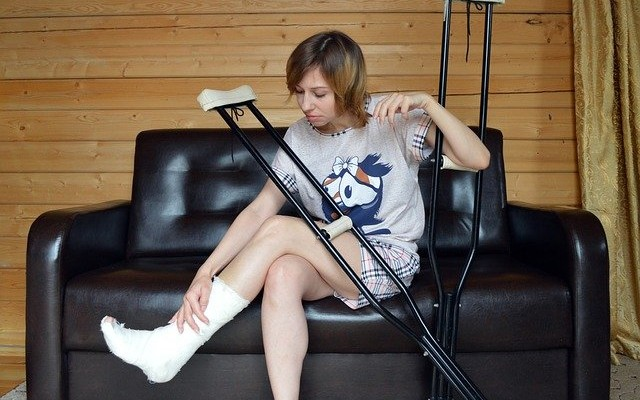 Mulher sentada em um sofá com gesso na perna e com muletas.