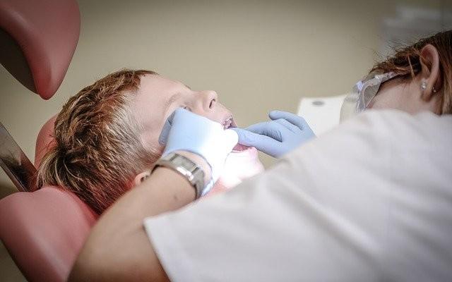 Dentista avaliando a saúde bucal de uma criança.