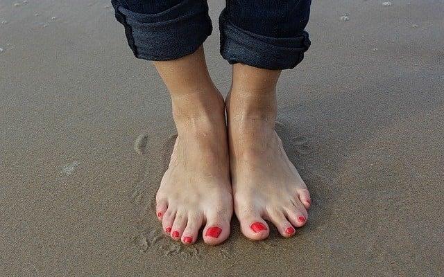 pés de uma mulher na areia.