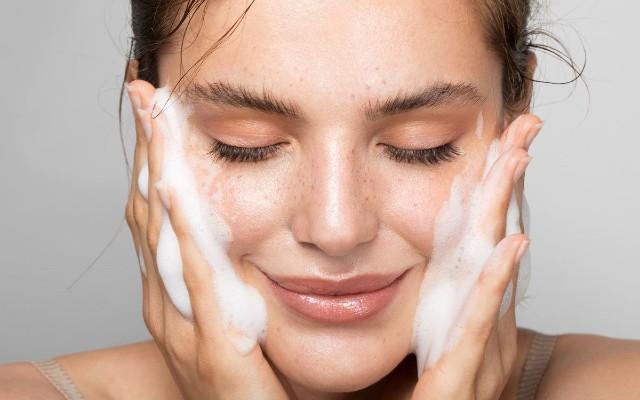 Mulher esfregando o rosto com sabonete para higienizá-lo.