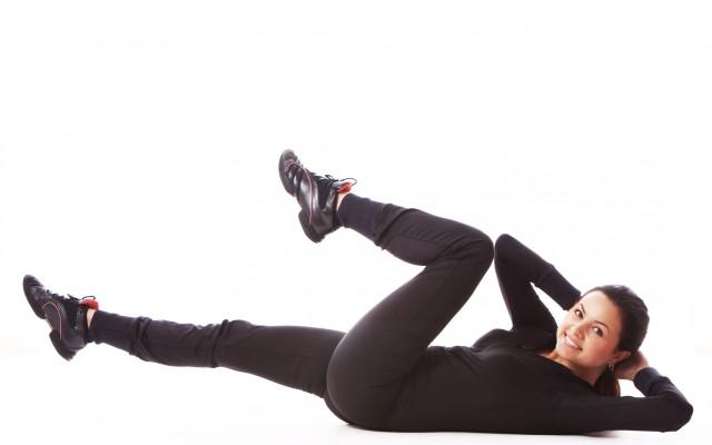 Mulher fazendo abdominal bicicleta.