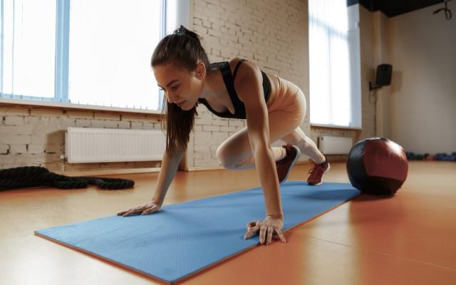 Mulher fazendo abdominal spider man. um dos tipos de abdominais.