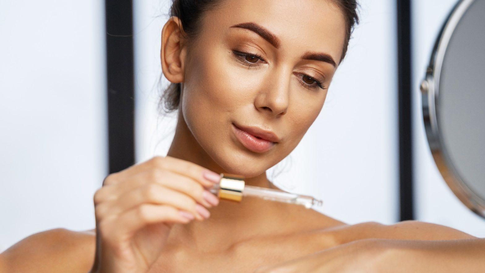 Mulher passando ácido hialurônico na pele.