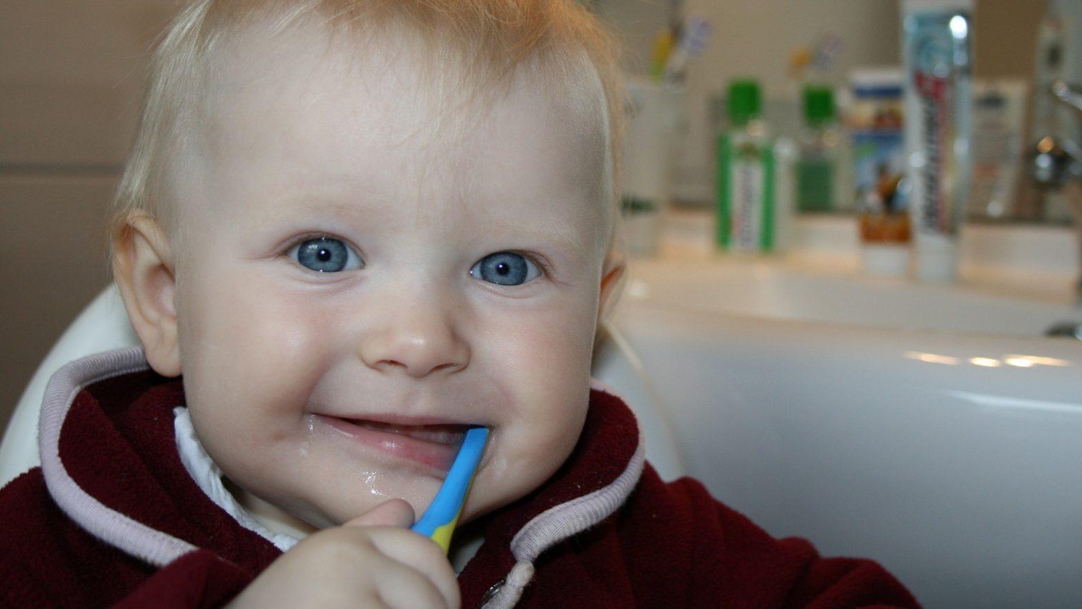 Bebê com escova dente na boca.