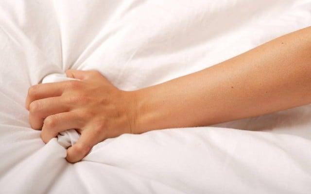 Mão de mulher agarrando o lençol.