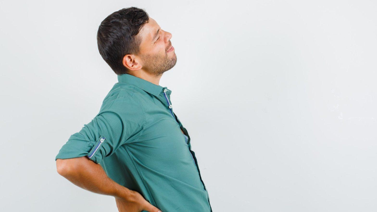Homem com as mãos apoiadas na lombar com expressão de dor.