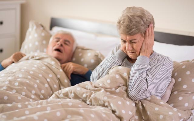 Mulher tampando os ouvidos para não escutar o marido roncando.
