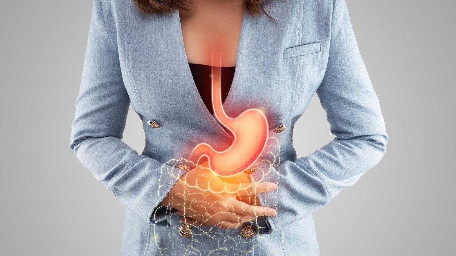 Mulher com as mãos na barriga, e desenho do aparelho digestivo.