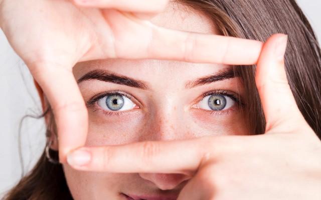 Mulher fazendo um retângulo com as mãos ao redor dos olhos.