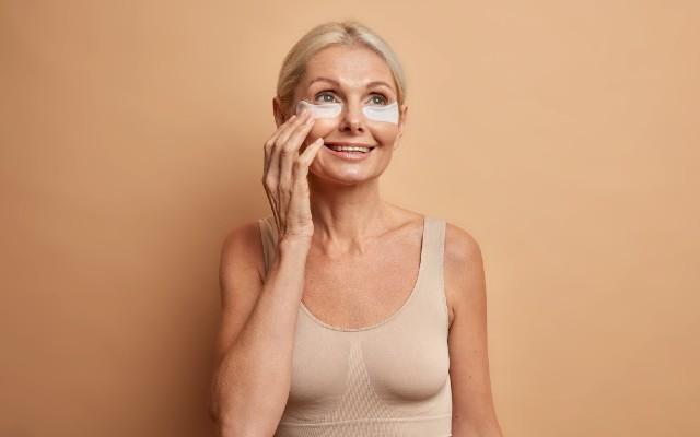 Muher mais velha aplicando creme hidratante na região dos olhos.