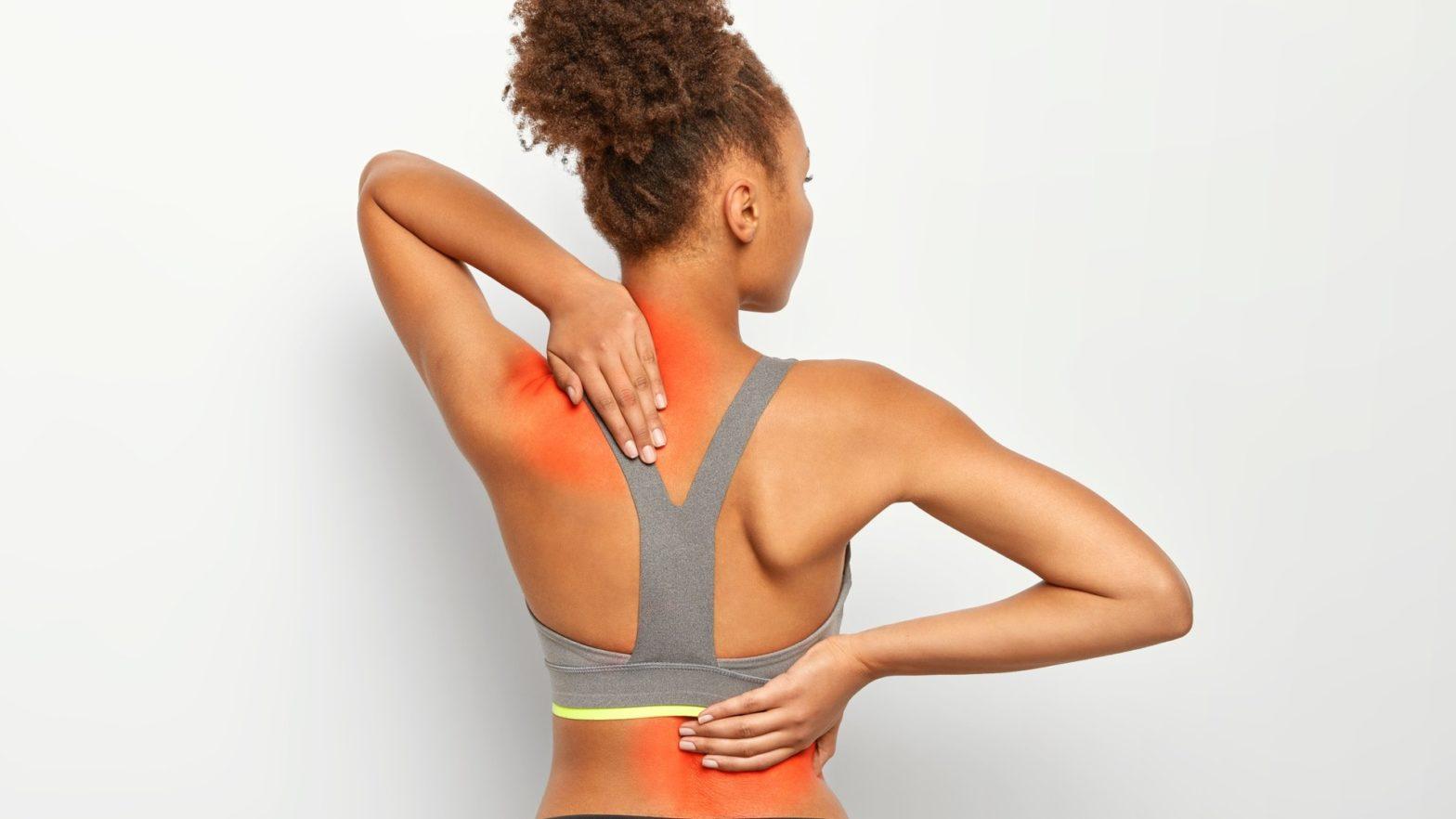 Mulher com dor na lombar e nos ombros.