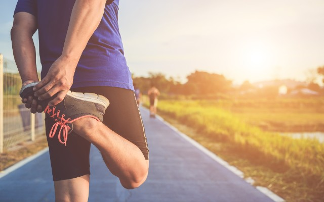 Homem alongando as pernas para começar a correr.