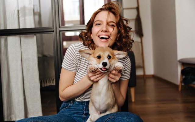 Mulher sorrindo segurando seu pet.