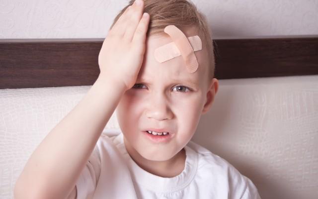 Menino com a mão na cabeça sentindo dor.