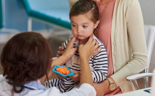 Médica pediatra examinando menina.
