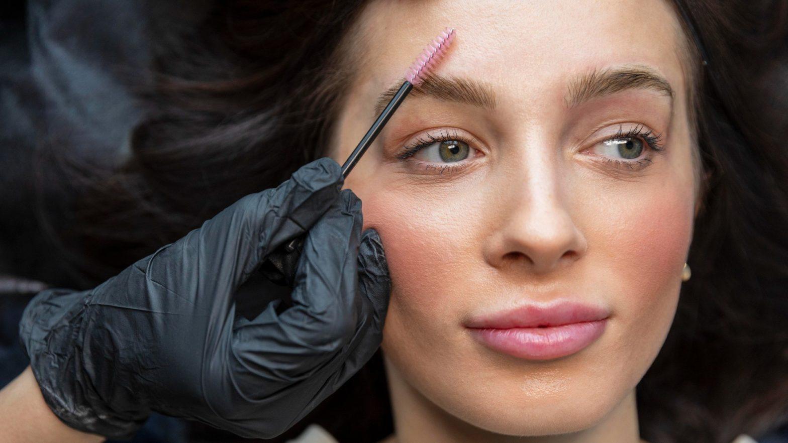Mulher fazendo brow lamination em cliente.