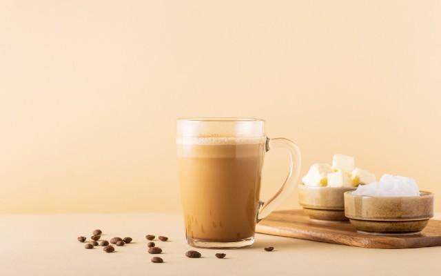 Xicara de café com recipientes ao lado de manteiga e óleo de coco.