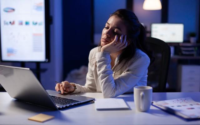 Mulher com semblante de sono em frente ao computador.