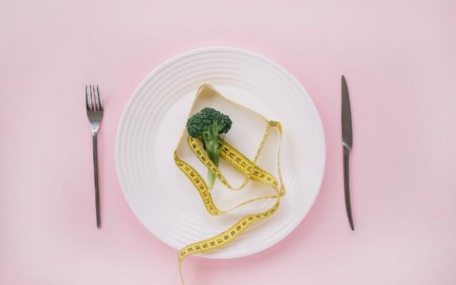 Prato com fita métrica e um brócolis.