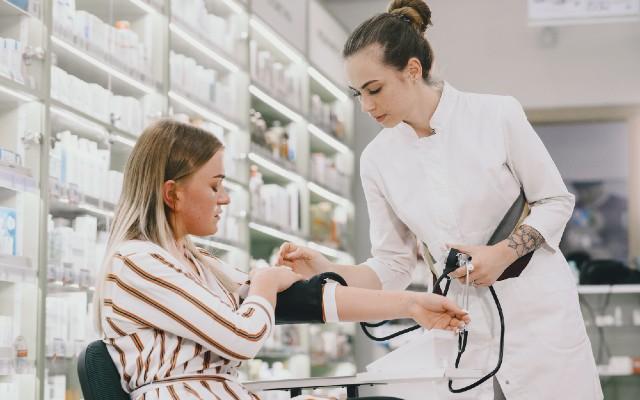 Médica conferindo a pressão arterial de paciente.
