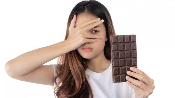 Mulher com semblante desconfiado olhando uma barra de chocolate.