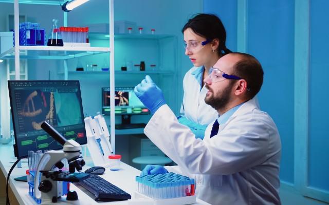 Biomédicos analisando em laboratório fragmentos de DNA.